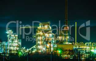 Chemical Factory w illumination, tubes and buildings at night - near