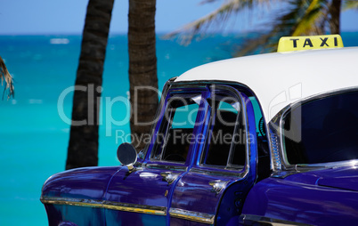 Oldtimer taxi in front of palms at the sea