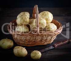 fresh potatoes in a peel lay in a brown wicker basket