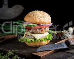 cheeseburger with vegetables on a brown old wooden board