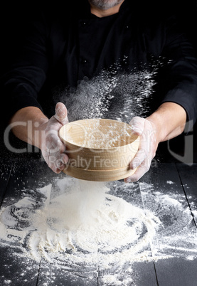 round wooden sieve with flour in male hands