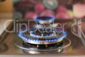 Gas stove with blue flame. Stove with a lit burner