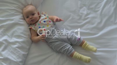 Active baby girl on bed at home