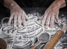 men's hands stir the white wheat flour