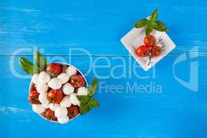 Mozzarella, cherry tomatoes and basil in a bowl seen from above