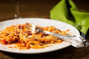 Closeup of half-eaten tagliatelle pasta with bolognese ragu