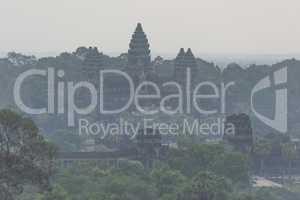 Misty ruins of Angkor Wat among trees