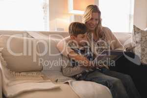 Mother with her son reading story book in living room