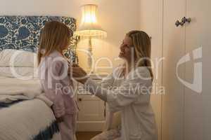 Mother helping her daughter in wearing nightwear