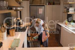 Mother with her daughter removing muffin cakes from oven in kitchen