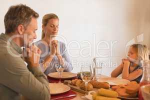 Family praying before having dinner on dining table