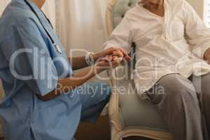 Mid section of female physician consoling senior woman