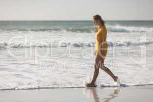 Woman walking on the beach near seashore