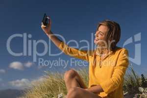 Woman taking selfie with mobile phone at beach