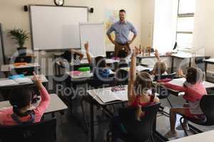 School kids raising hand in classroom