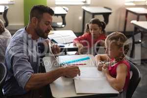 Young school teacher helping girl with study in classroom
