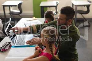 Young school teacher helping girl with study on laptop in classroom