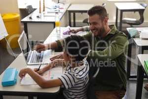 Young school teacher helping boy with study on laptop in classroom