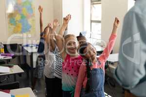 School kids standing in row and raising hand in classroom