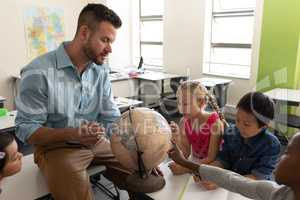 Side view of male teacher teaching his kids about geography by using globe in classroom