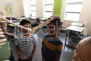 School kids playing with skeleton in classroom