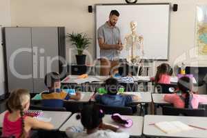 Far sight of male teacher explaining human skeleton model in classroom