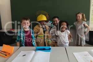 Happy male firefighter with schoolkids looking at camera in classroom