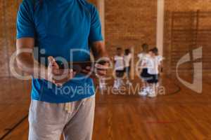 Mid section of basketball coach using digital tablet at basketball court