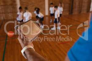 Basketball coach using digital tablet at basketball court in school