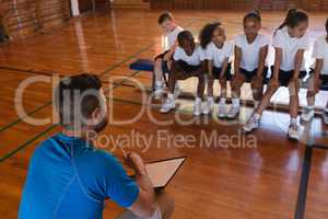 Basketball coach talking with schoolkids at basketball court