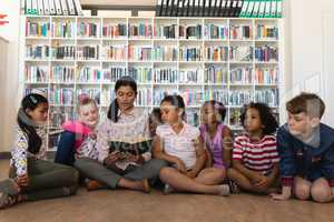 Female teacher teaching schoolkids and sitting on floor of school library
