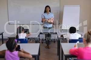 Female teacher explaining anatomy of body parts in classroom