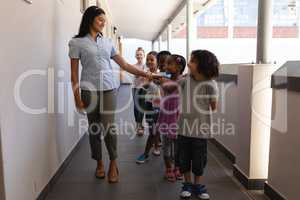 Schoolkids with teacher standing in row with their hands on shoulder in hallway