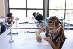 Schoolgirl drawing on book at desk in classroom
