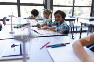 Schoolboy sitting at desk and looking at camera in classroom