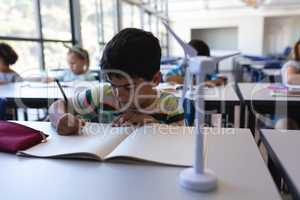 Schoolboy writing on notebook at desk in classroom