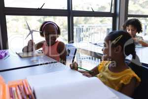 Happy schoolkids talking with each other at desk in classroom