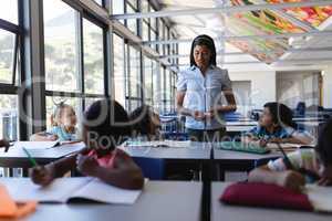 Female teacher teaching student at desk in classroom