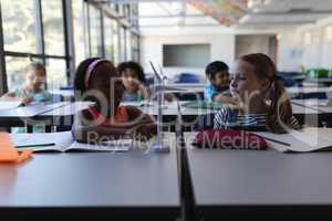 Schoolkids studying on windmill model at desk in classroom