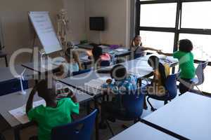 Schoolkids studying at desk in classroom