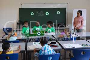 Schoolkids studying about green energy and recycle at desk in classroom