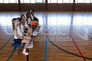 Schoolkids sitting on bench at basketball court