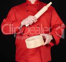 cook in a red uniform holding a wooden rolling pin and round sie