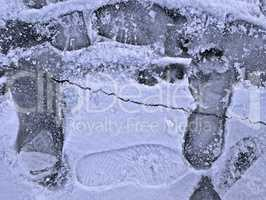 Frozen pond surface with footprints close-up
