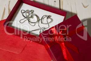 Closeup of silver heart pendants in a red gift box and a red env