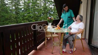 Care worker spending time with old lady in her home