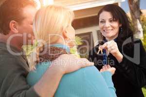 Hispanic Female Real Estate Agent Handing Over New House Keys to