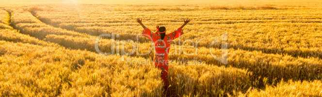 African woman arms raised in a field of crops at sunset or sunri