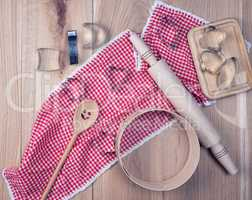empty round wooden sieve and rolling pin on a red textile kitche