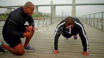 Smiling bald man motivating his friend who doing push ups